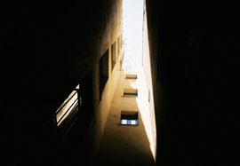 Photo looking up, skywards, between tall buildings on a narrow street in Girona, Catalonia